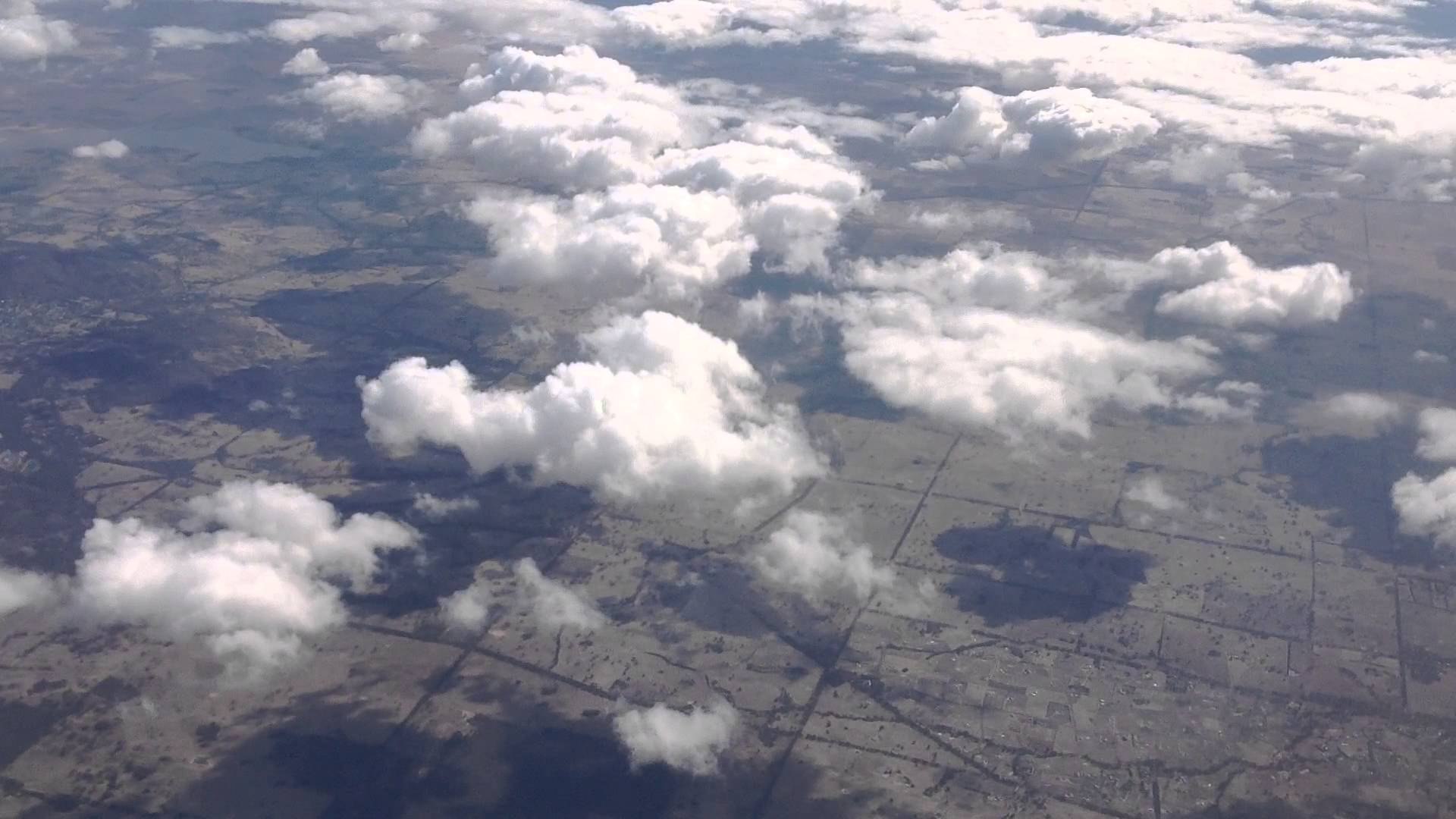 Ground seen from the sky on top of the clouds